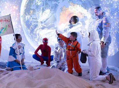 Make-A-Wish Australia wish kid Dwayne wearing his NASA spacesuit on the moon with other space characters