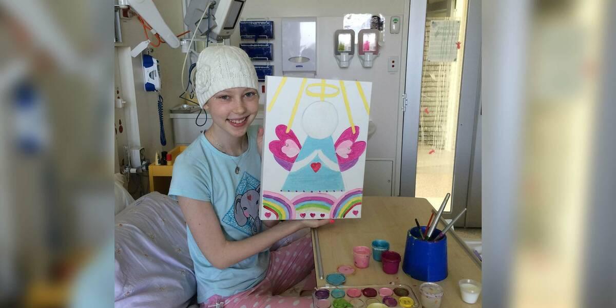 Make-A-Wish Australia wish kid Tara in hospital holding up a painting