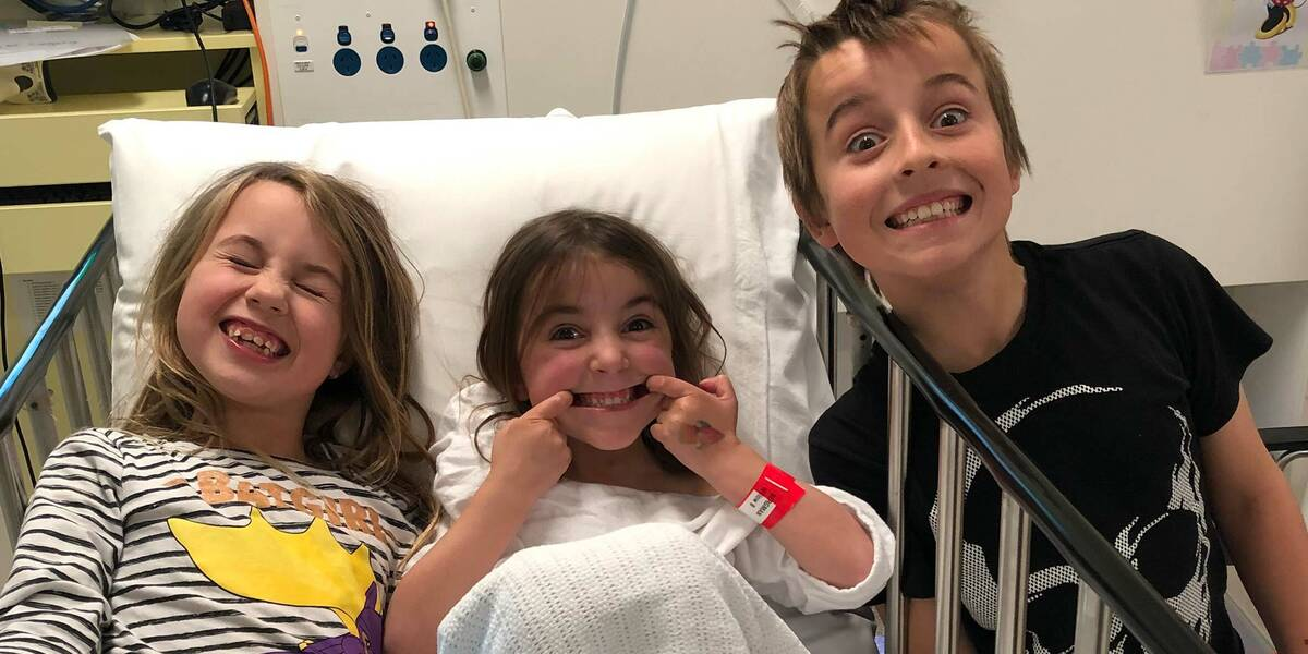 Make-A-Wish Australia wish kid Willow lying in a hospital bed with her brother and sister, pulling funny faces