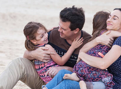 Make A Wish Australia Children's Charity - Audrey with her family hugging on the beach