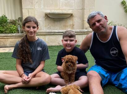 Make-A-Wish Australia wish kid Carmelo sat with his family and new cavoodle