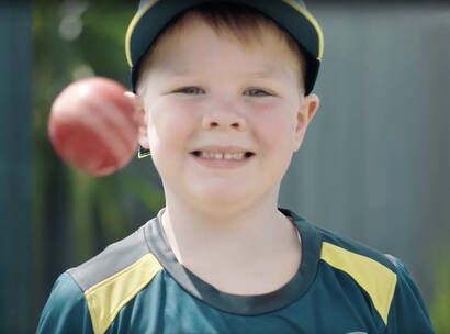 Archie tossing a cricket ball in his cricket kit