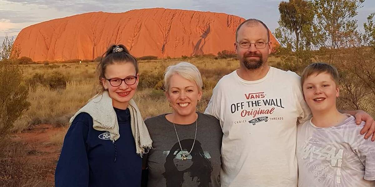 James and family standing in front of Uluru
