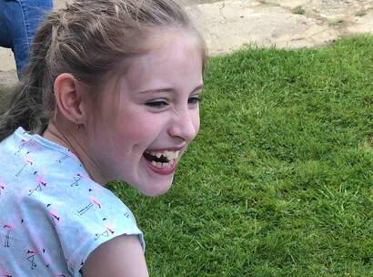 Make-A-Wish Australia wish kid Grace sat smiling in garden