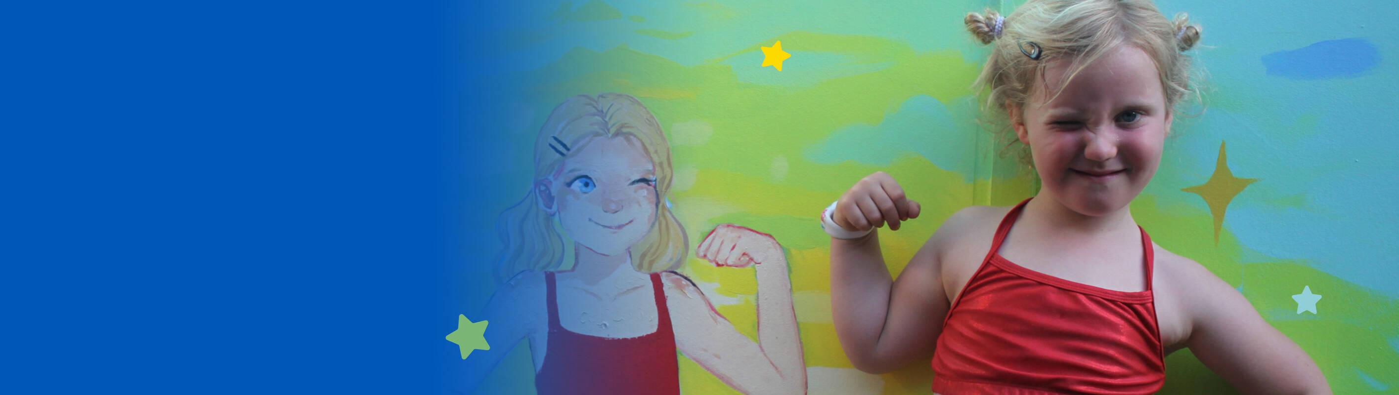 Make-A-Wish Australia wish kid Juniper in front of her ninja warrior inspired mural