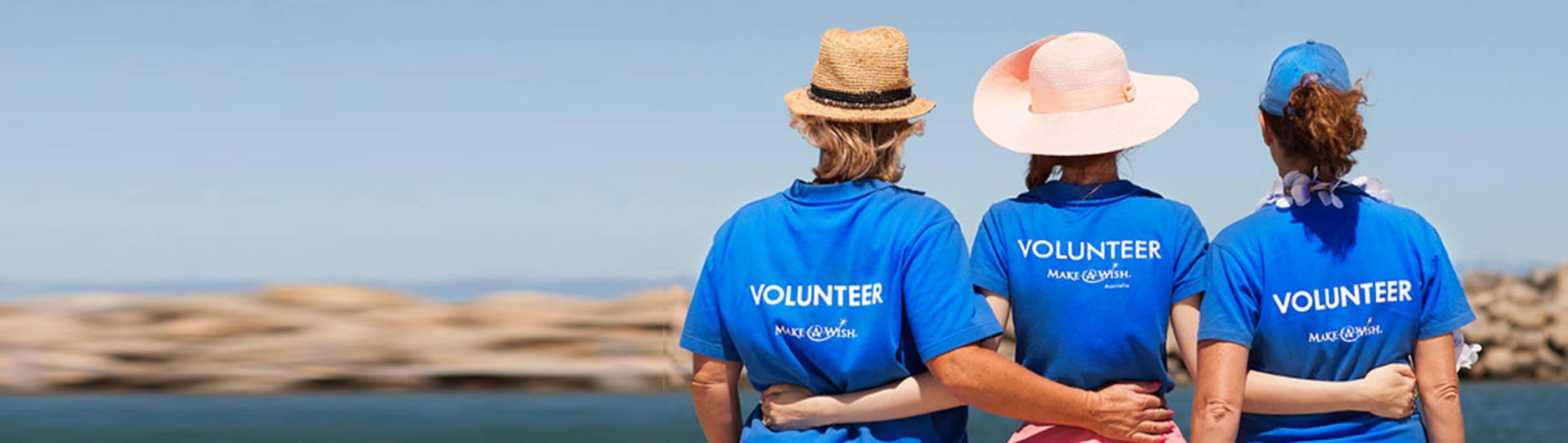 Make A Wish Australia, Children's Charity - The back of volunteers hugging wearing Make A Wish T-shirts