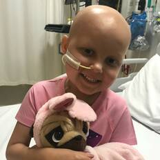 Make-A-Wish wish kid Lexie in hospital holding a toy